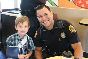 Officer with young boy that has his arm in a sling